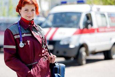Positive female paramedic with ambulance