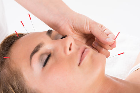 Closeup of hand performing acupuncture therapy on head and chin at salon