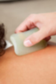 Detail of back fo young male receiving gua sha acupuncture treatment