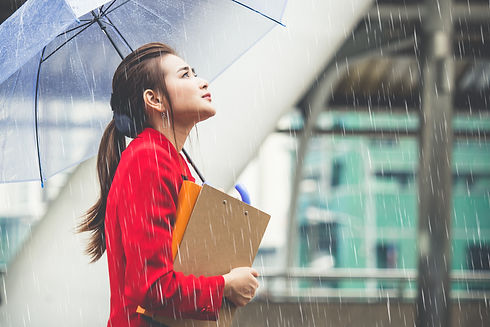 Young asian businesswoman holding business documents and umbrella walking under raining in the city