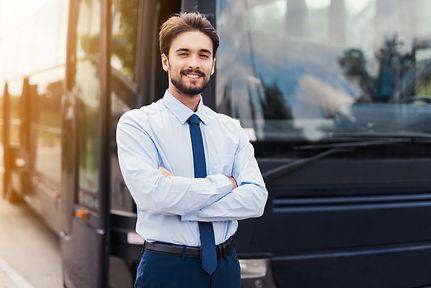 male-driver-smiling-posing-against-black
