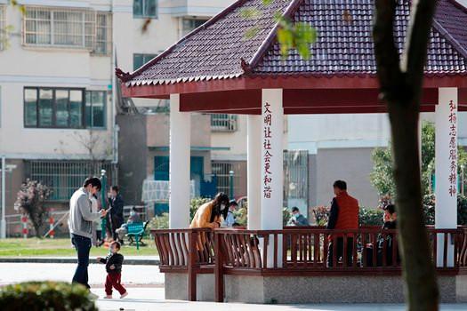 图为上海金湾佳园小区居民带着孩子在小区内活动。 (图片来源:中新社)