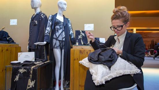 图为意大利某知名服装品牌的一位技师在手工缝制一件睡衣。(图片来源:中新社)