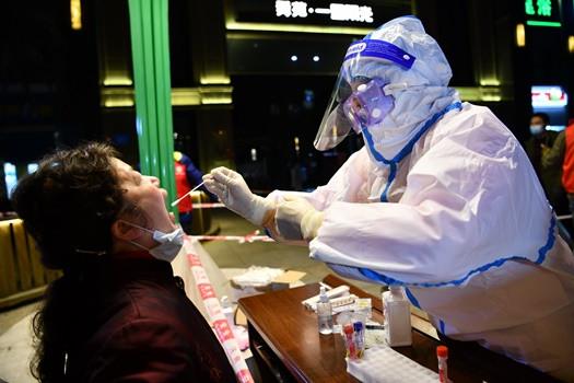 12月9日晚,成都市郫都区一小区外,居民排队接受核酸检测。 (图片来源:中新社)