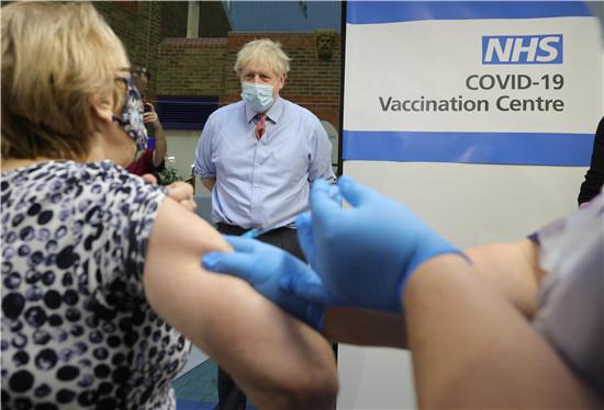 12月8日,英国首相鲍里斯·约翰逊在伦敦一家医院的疫苗接种中心观看一名女子接种疫苗。(图片来源:新华社)