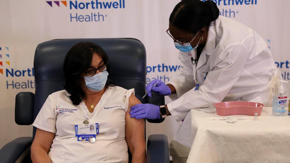 在美国纽约长岛犹太医疗中心,护士斯蒂芬妮·凯尔(左)接种新冠疫苗。(图片来源:新华社)