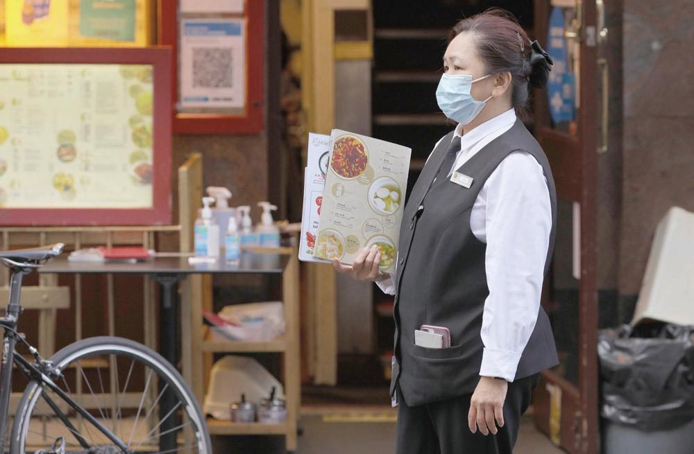 1月1日,一名餐厅员工在伦敦中国城等待顾客。(图片来源:新华社)