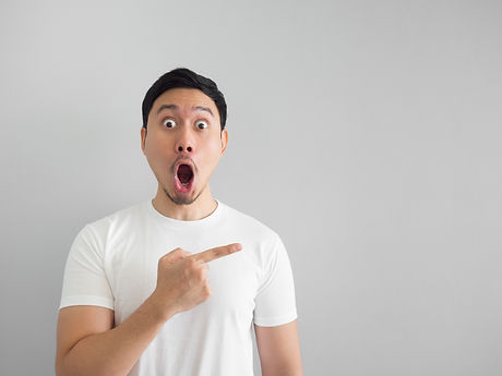 Shocked face of Asian man in white shirt on grey background..jpg