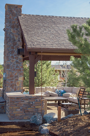 Fireplace, stone veneer, pillar, stained concrete patio, seat wall, planting, roof, chimney