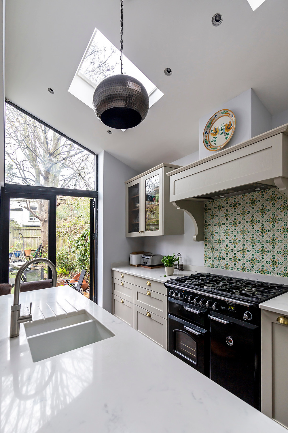 Kitchen island and range cooker with skylight and view to garden