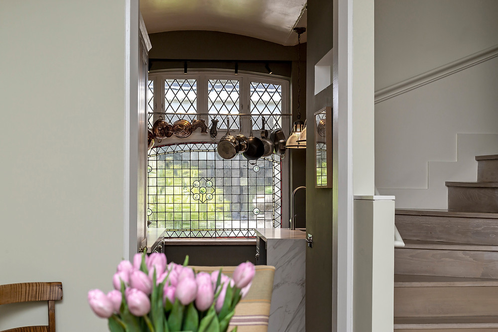 View into kitchen from dining room with stairs to right and pink tulips on table