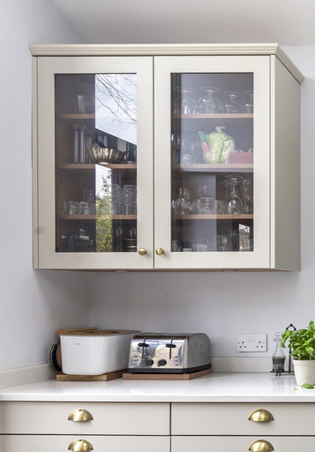Glass fronted wall cabinets with gold handles