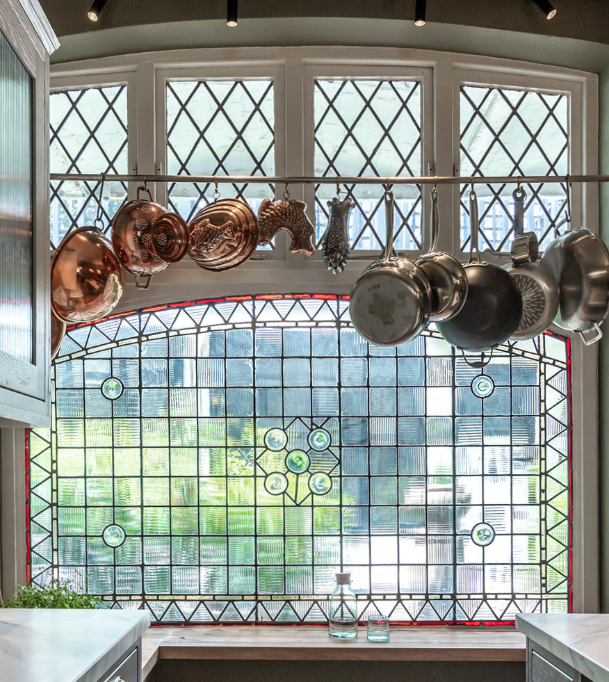 Paned glass window in mews kitchen with hanging copper jelly moulds and pans
