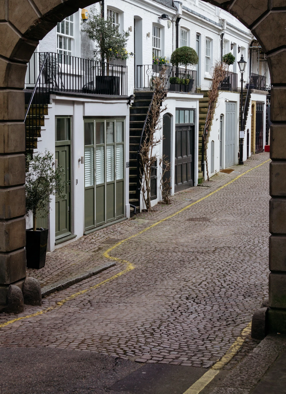 View through arch to contemporary mews street with external stairs to balconies