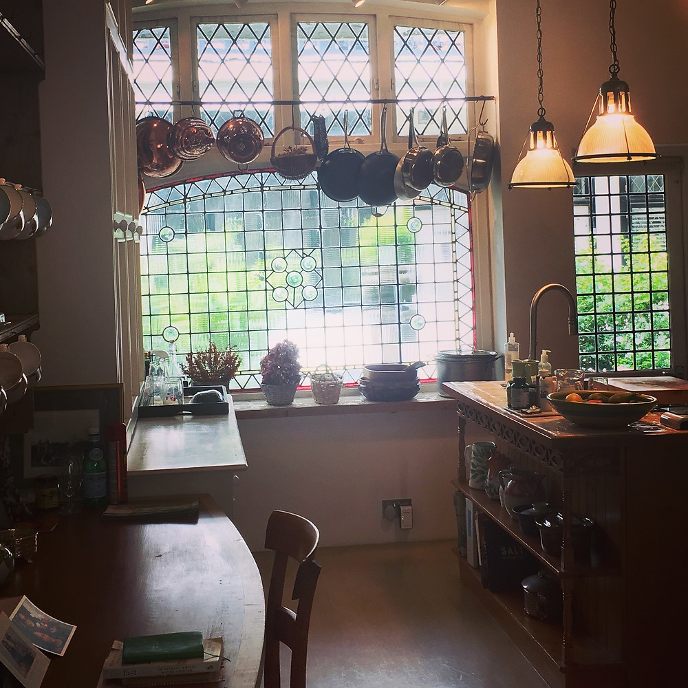 Kitchen before refurbishment with original paned window and brass pots and pans