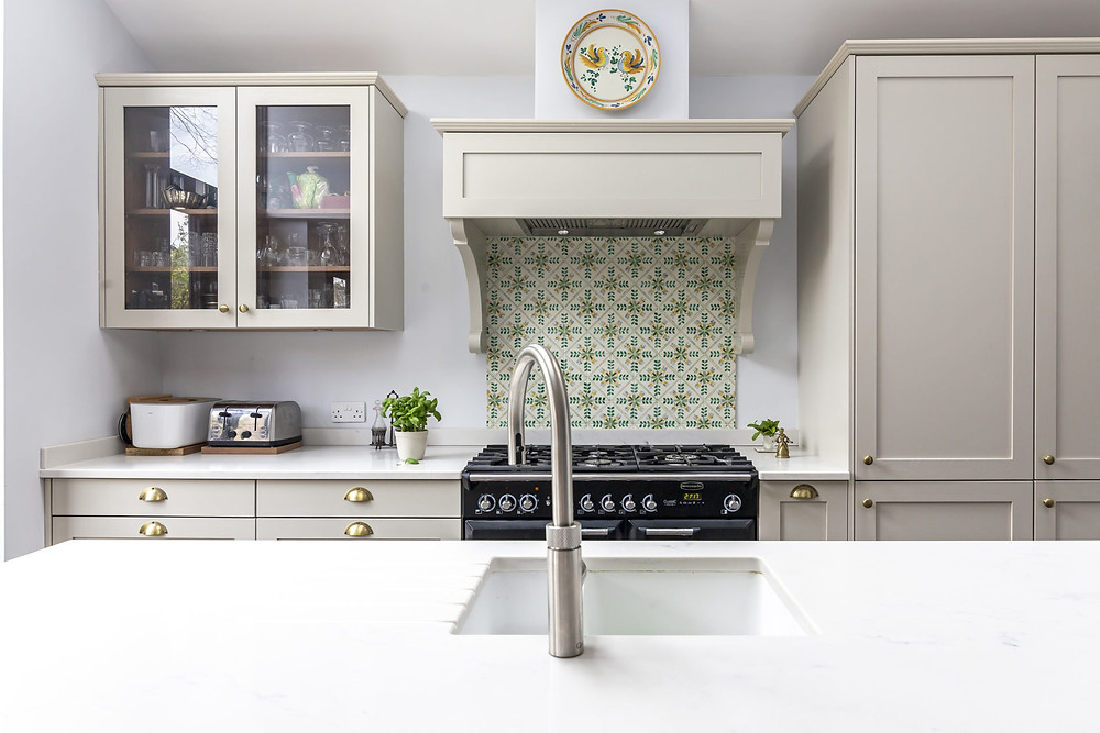 French style kitchen with tiled splashback and canopy hood above range cooker