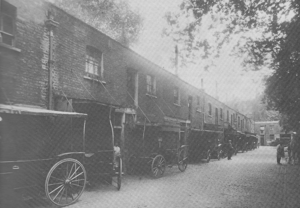 19th Century mews street with carriages outside waiting for horses
