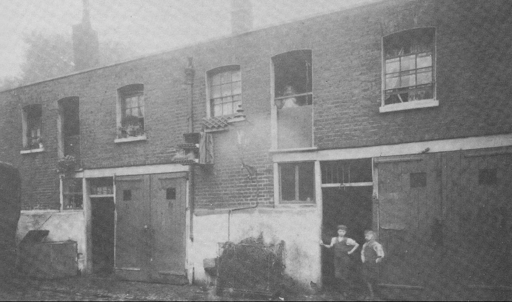 19th century mews street with stableboys outside and girl looking out of hayloft