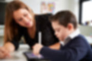 young-female-teacher-sitting-at-desk-wit