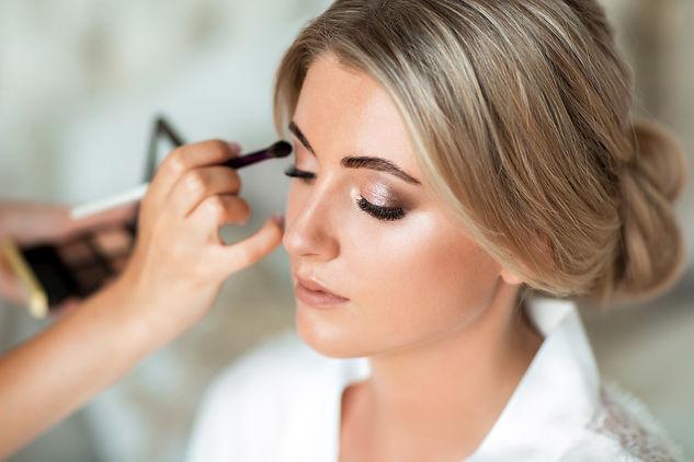 Makeup artist puts makeup beautiful brid