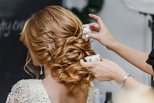 Hair stylist or florist makes the bride a wedding hairstyle with fresh cotton flowers
