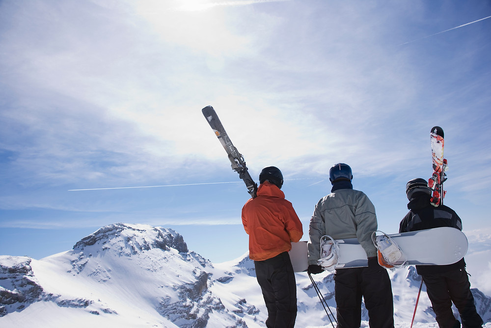 Two skiers and one snowboarder standing on top of a slope at Mammoth Ski Resort on a sunny day.
