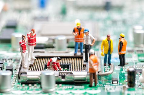 Team of engineers repairing circuit boar