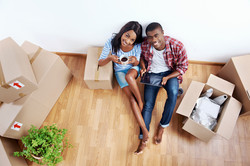 overhead view of young black african couple with moving boxes in new apartment using modern tablet c