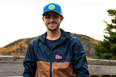 tuck windbreaker and blue hat smile 2 (1