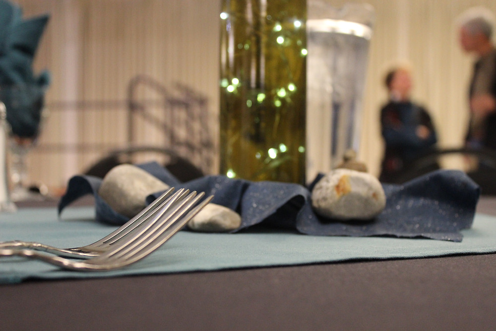 Photo 1: Dining set-up at Table 6, Annual RIverkeeper's Benefit Dinner. In the background are a pair of the speakers, jiving about clean water (presumably).