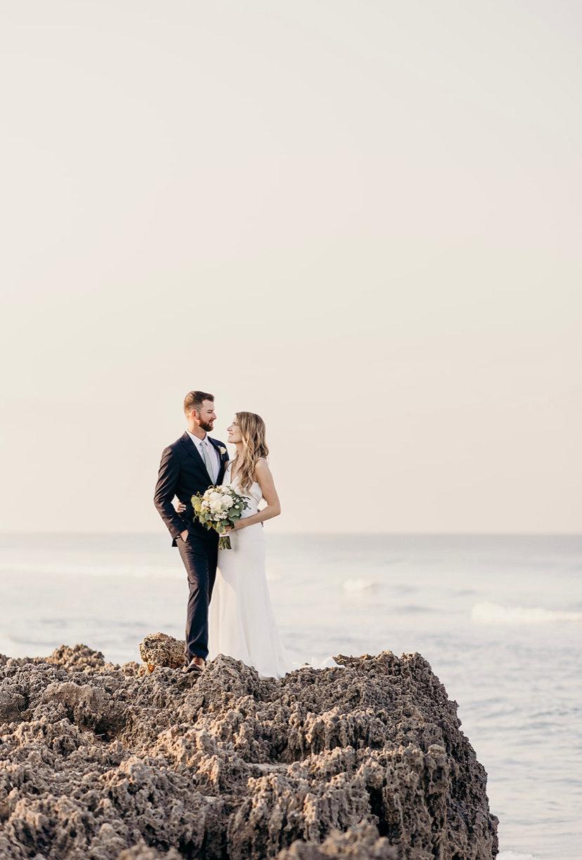 bride and groom on rock ledge.jpeg