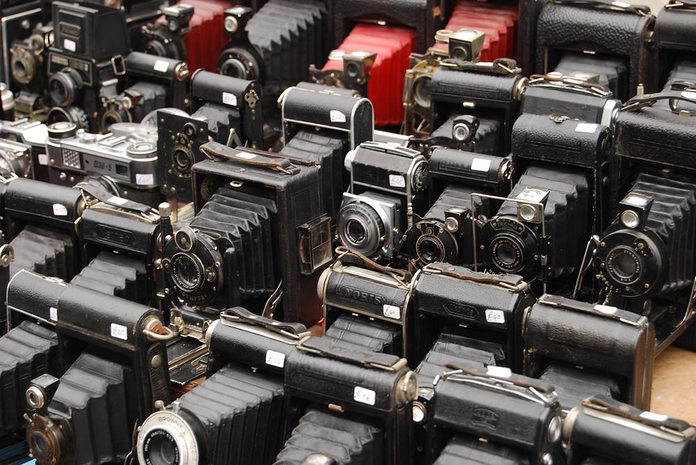 a dozen old-timey cameras
