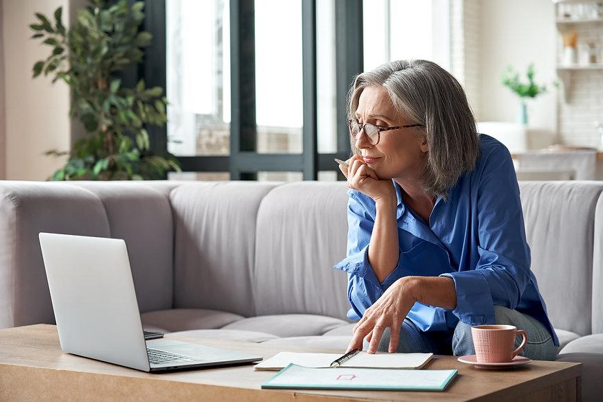 Senior mature older woman watching busin