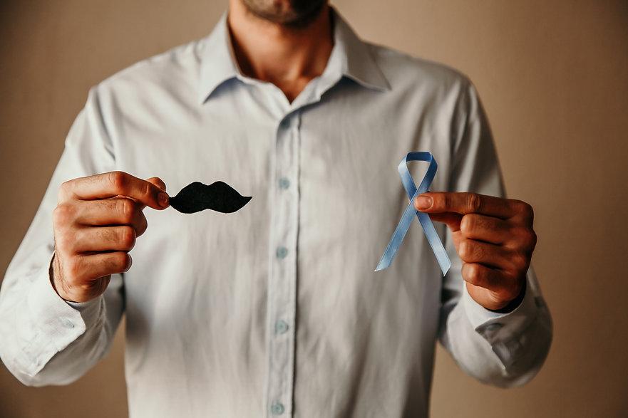 man-doctors-hands-holding-a-blue-ribbon-