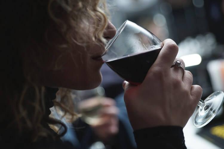 Blonde Frau nippt an Glas Rotwein
