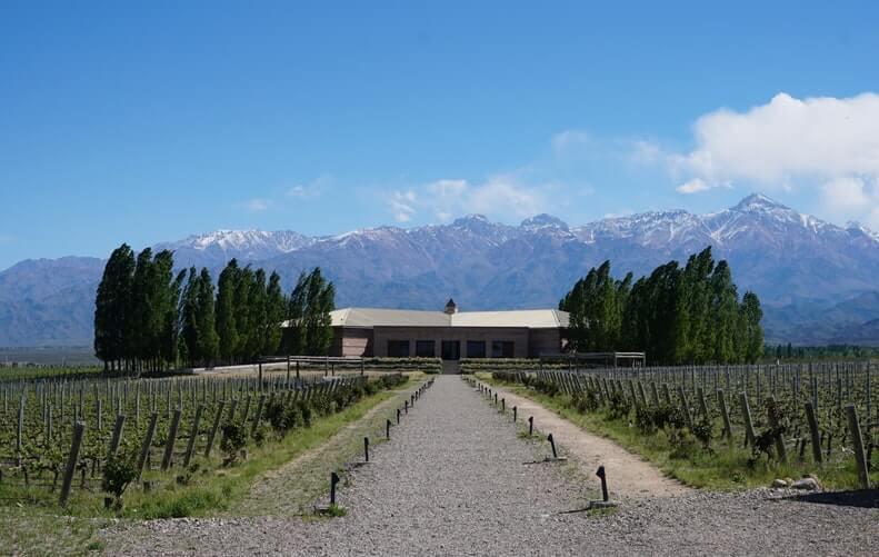 Graues Haus auf Weingut in Argentinien mit blauen Bergen im Hintergrund