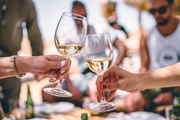 Anstoßen mit zwei Gläsern Weißwein