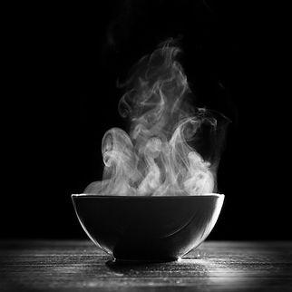 Bowl of hot soup on black background.jpg