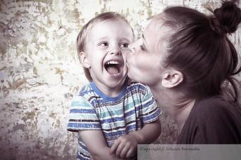 Mom kissing little son