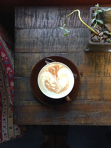 A frothy latte, resting on a dark wood table, and shot from above