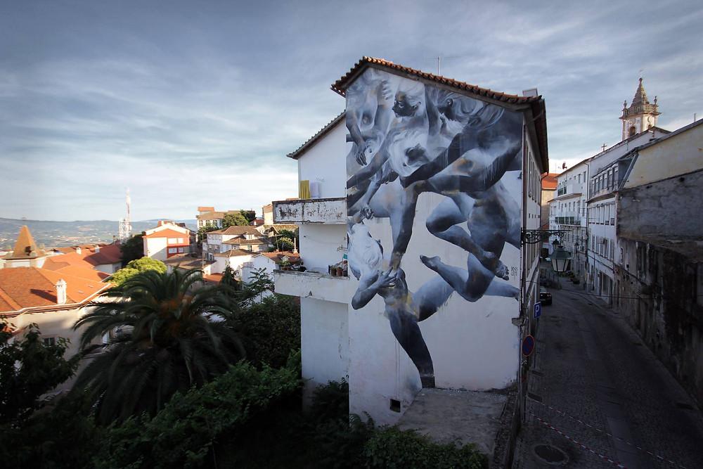 Mural de arte urbana na lateral de um prédio no centro histórico da Covilhã com corpos entrelaçados retratados em negativo, sendo apenas possível ver a pintura final invertendo as cores da fotografia parte do festival de arte urbana WOOL