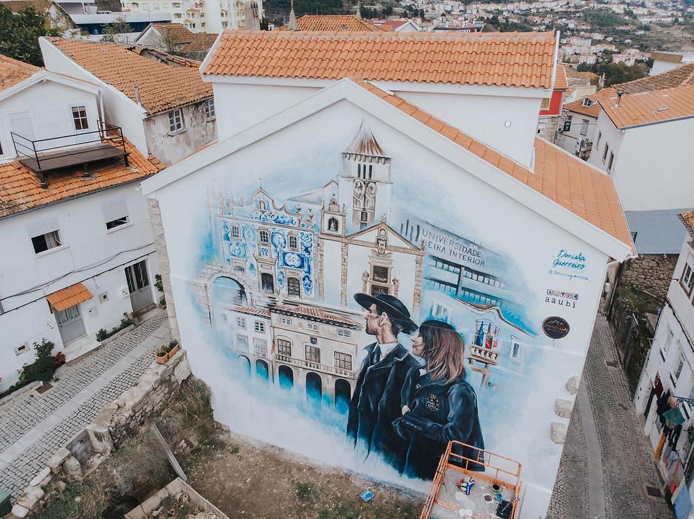 Vista aéra de mural de arte urbana fachadas de igrejas e edifícios da covilhã com 2 estudantes trajados a olhar para eles
