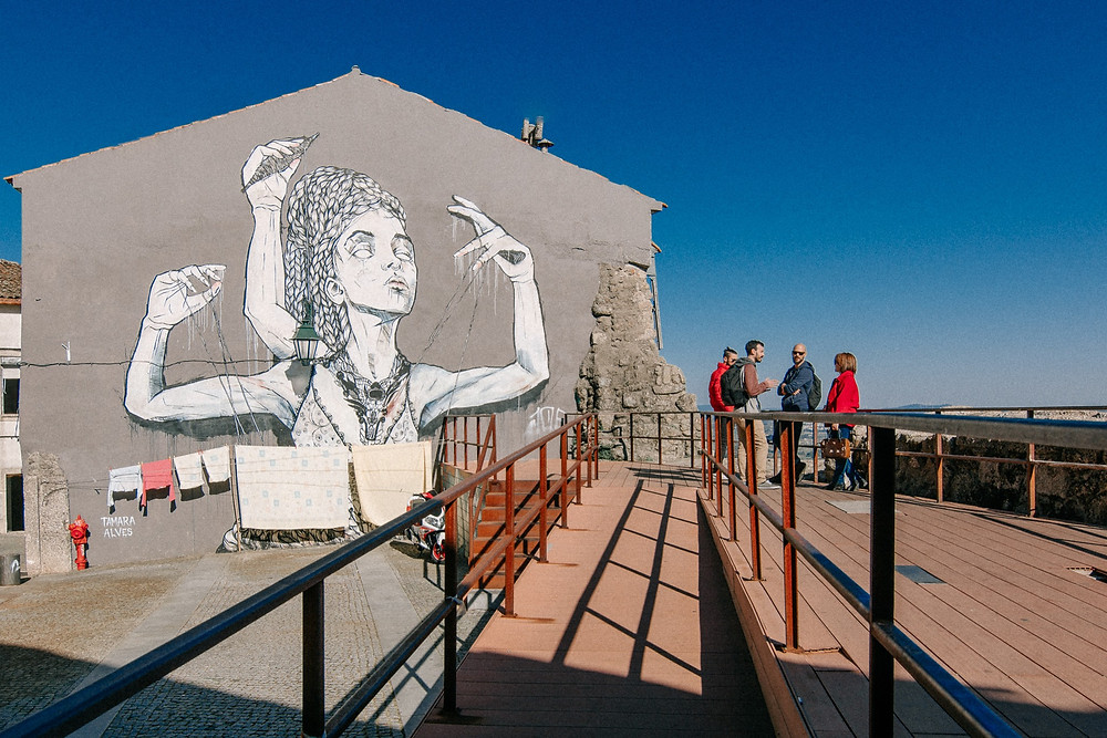 Mural de arte urbana da artista Tamara Alves que retrata uma mulher com 3 braços a tecer o seu prórpio fio, alusiva aos lanifícios da cidade da Covilhã, numa parede junto ao Miradouro das Portas do Sol com 4 pessoas a conviver no miradouro