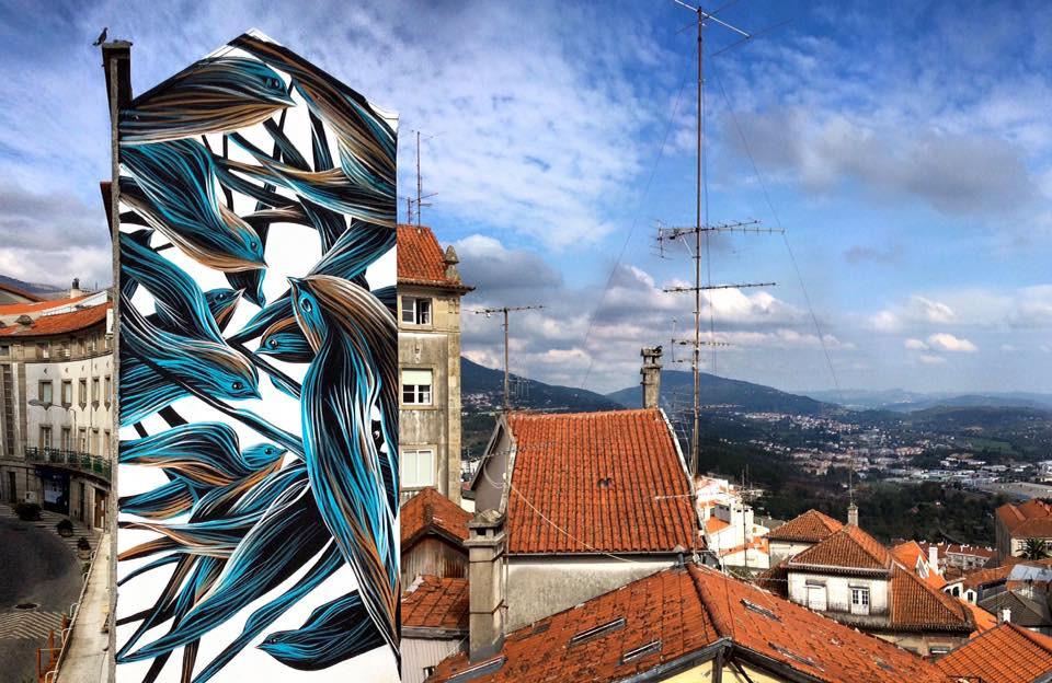 Mural de arte urbana de andorinhas estilizadas em tons de azul e castanho pelo artista Pantónio na lateral de um edifício alto e esguio na Rua Comendador Campos Melo no centro da Covilhã com vista ao longe dos arredores da cidade e céu azul