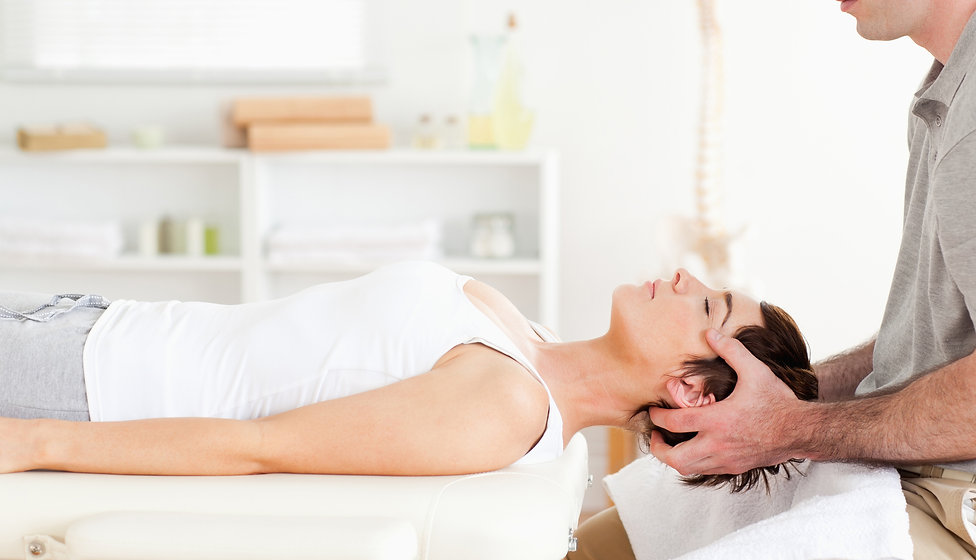 Woman having neck adjusted by a chiropra