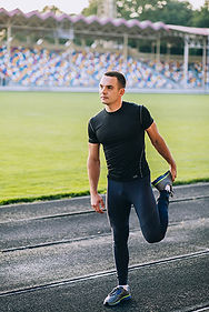 Man_stretches_injuried-leg_before_runnin