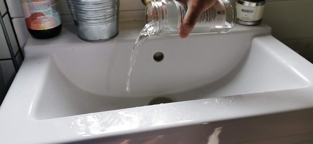 A man rinses out the jar which contained the infused vinegar and mixes with a little water to rinse his sink to use every last drop of the vinegar mix.
