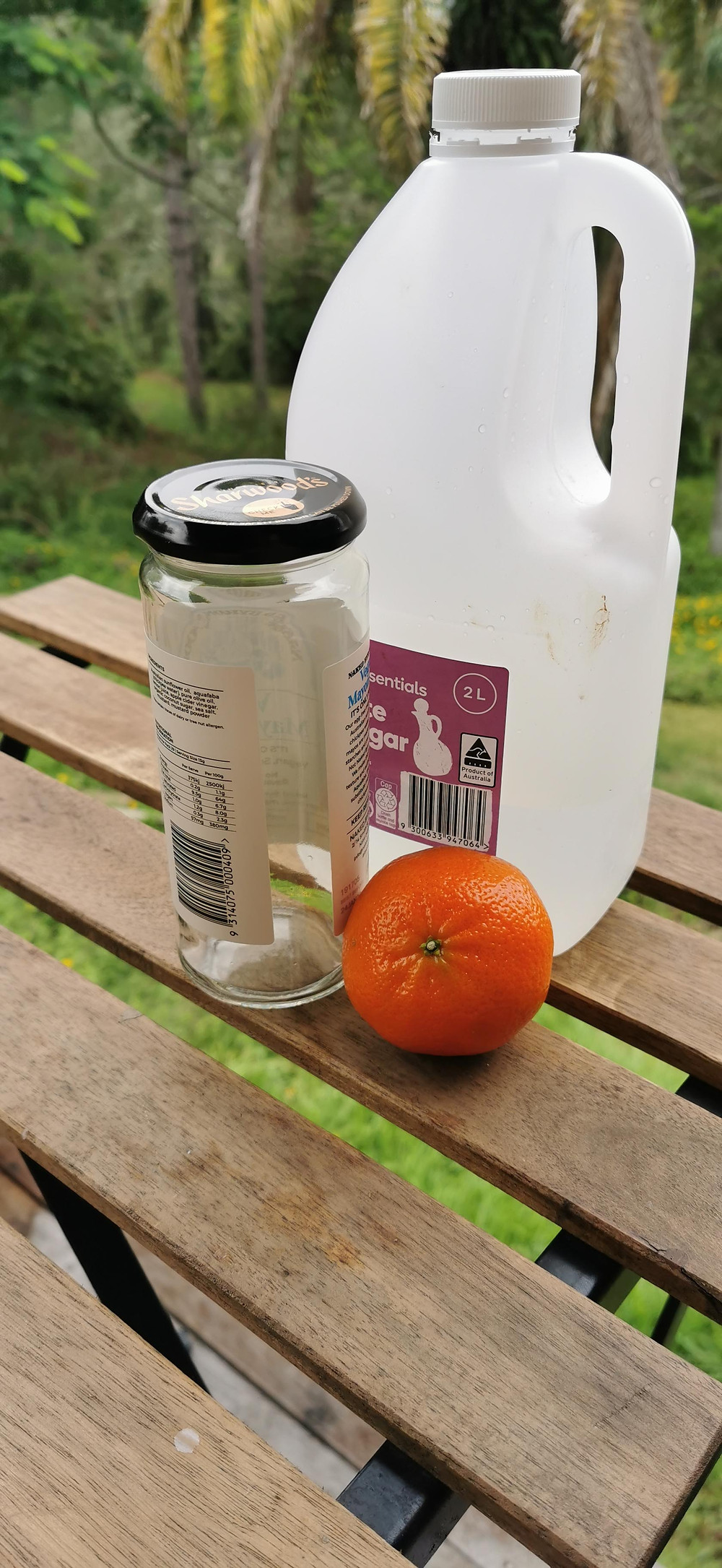 three ingredient all purpose spray. Natural ingredients preset are white vinegar, a mandarin and an old repurposed glass jar
