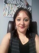 Photo de la psychologue Adeline Doby, souriante, assise à son burau.