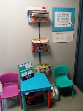 Photo du coin enfants de la salle d'attente : deux petites chaises, des magazines et des livres.